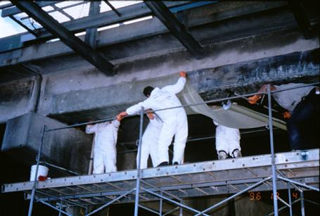 Workers installing a GFRP fabric to strengthen deteriorated reinforced concrete T-beam