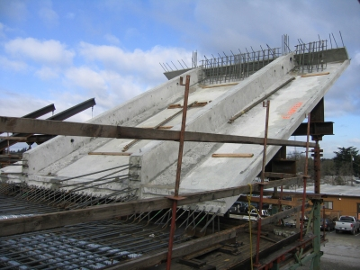 A side panel made of lightweight concrete and cast separately is placed in the casting bed and tied into the soffet reinforcement of the segment.