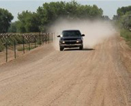 truck driving down a very dusty unpaved road