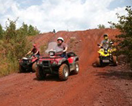 Three  people riding OHVs in a nature setting
