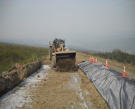 road crew applying wicking fabric to muddy section of road