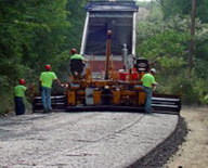 road crew applying driving surface aggregate