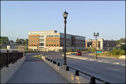 Photo of the approach into the ne Phalen Boulevard from the west over the first bridge structure.  The corridor includes decorative street lights and aesthetic bridge railing.  The roadway leads into an area with new business park developments.