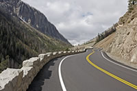 Stone guardwall accentuates the curvilinear alignment as the East Entrance Road enters Sylvan Pass. Widened and deepened ditches along the erosive cut slopes minimize rockfall hazards.