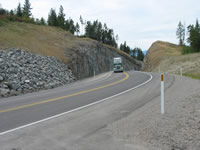 Large truck passing through large thru cut. Completion of Flowery Trail has opened a new corridor for industry.
