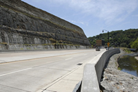 Photo of the new pavement cross-section with a high rock cut slope on the left and the new retaining wall on the right.
