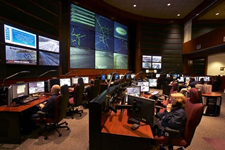 GDOT's Traffic Management Center Operations Floor, with computer workstations for staff and a wall of screens for viewing data and live images of traffic and roadway conditions.