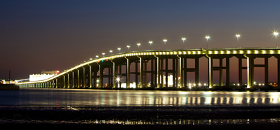 Photo showing the long, flowing curves to accommodate marine traffic under the Biloxi Bay Bridge, lighted against the night sky.