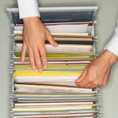 Image of file cabinet drawer with hands checking a folder