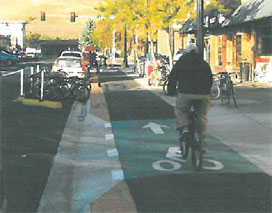 Photo of a bicyclist traveling on a one-way cycle track, which is physically separated from street traffic.