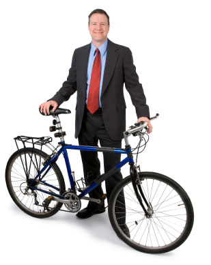 Photograph of a man in a business suit standing next to a bicycle.