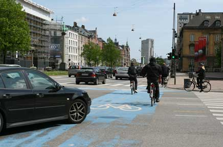 Photo of a car turning right through bicycle crossing after cyclists have passed through.