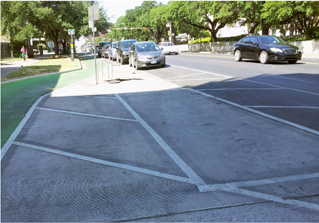 One-way green painted separated bike lane on two-lane, one-way street in Austin, TX. Separated bike lane bends towards sidewalk curb creating accessible parking space in painted buffer between bike lane and street. On-street parking and reflective delineator posts installed on painted buffer between bike lane and street. Painted buffer between accessible parking space and street.