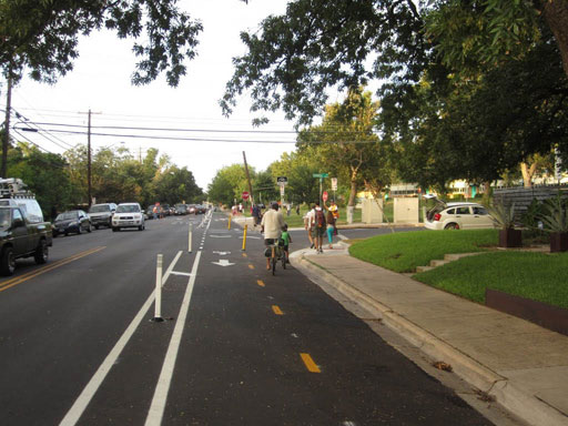 Two-way separated bike lane in residential area on Bluebonnet Lane that is part of a low-stress bicycle network in Austin, TX. Separated bike lane is at street-level with the same paved asphalt surface treatment as the vehicle travel lanes and a yellow dashed line separating the bicyclist direction of travel. Painted buffer with plastic reflective delineator posts separates the two-way bike lane from the vehicle travel lanes. White painted arrows on the surface indicate direction of travel and white dashed lines indicate crosswalks and intersections.
