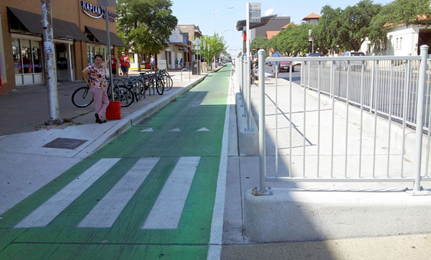 One-way green painted separated bike lane on left-side of three-lane, one-way street in Austin, TX. Concrete island bus platform between bike lane and street. Ramp deployment area adjacent to bike lane on curbside with painted crosswalk markings from curb to island bus platform. Bike rack adjacent to ramp on sidewalk.