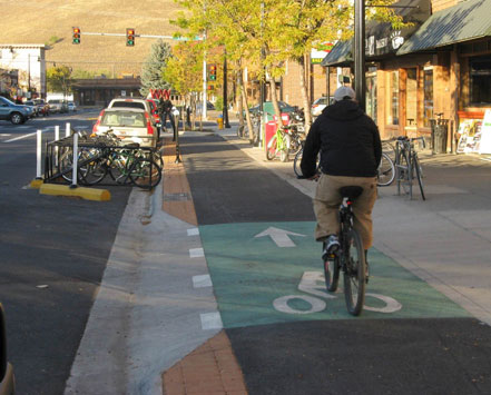 Raised one-way separated bike lane with curbside bicycle and car parking providing vertical and horizontal separation from vehicular traffic on Higgins Street in Missoula, MT. Buffer with stamped brick surface between paved bike lane and curb.
