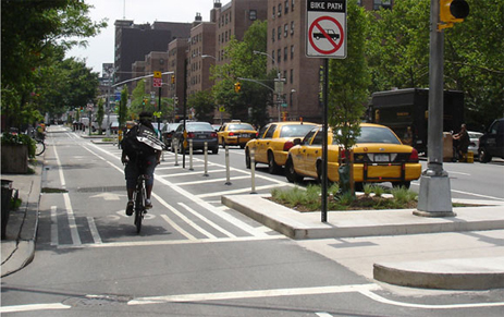 One-way separated bike lane on left-side of two-lane, one-way portion of 9th Avenue in New York City. Raised curb refuge islands at intersections combined with flexible bollards in painted buffer and parked cars between bike lane and street.