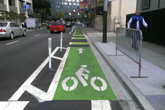 Image depicts separated bike lane on right-side of two-lane, one-way street with green paint and painted buffer with delineator posts.