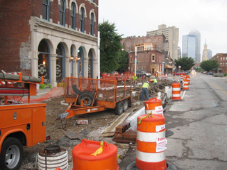 Construction of the downtown Cultural Trail in Indianapolis, IN shows equipment and orange traffic barrels along the street shoulder.