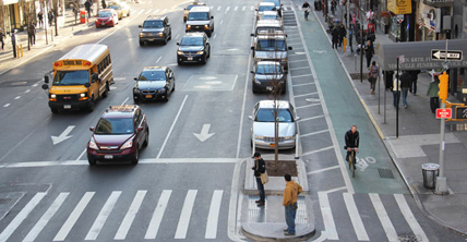 Pedestrians waiting to cross 1st Avenue in New York City on a median island refuge. Painted buffer and on-street parallel parking is between the street and a separated one-way bike lane at street level and treated with green thermoplastic paint.