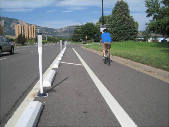 Image depicts one-way separated bike lane on right-side of three-lane, two-way Baseline Road in Boulder, CO. Continuously spaced parking stops and reflective delineator posts installed in painted buffer between bike lane and street.