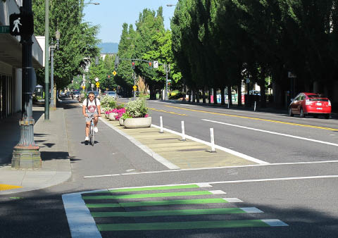 Image depicts two-way separated bike lane on left-side of three-lane, two-way street in Portland, OR. Painted buffer with reflective delineator posts and continuously spaces street planters between bike lane and street.