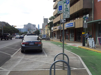 Image depicts one-way green painted separated bike lane on right side of two-lane, one-way street in Austin, TX. Reserved parking sign indicates accessible parking spaces between bike lane and vehicle travel lanes. Painted buffer between bike lane and accessible parking spaces.