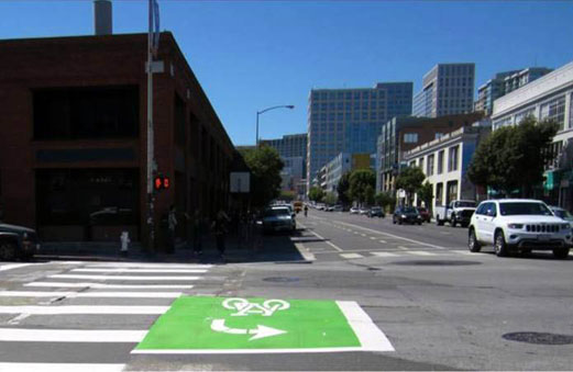 A green two-stage turn queue box is located to the left of the bike lane and prior to the pedestrian crosswalk.