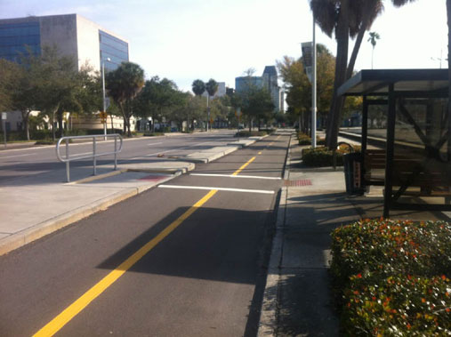 Platform island bus stop and two-way separated bike lane at 1st Avenue South in St. Petersburg, FL. A raised concrete median is between the bike lane and vehicle travel lanes. The bike lane is asphalt and has a solid yellow line separating direction of bicycle travel and a solid white standard crosswalk from the sidewalk to bus stop platform island.