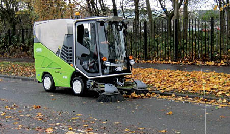 Narrow street sweeper capable of fitting into most separated bike lanes. Street sweeper is cleaning leaves along the shoulder of a residential street.