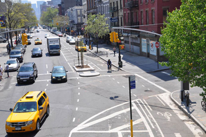 Transition from a buffered bike lane to one-way separated bike lane at intersection and on left-side of two-lane, one-way street portion of 8th Avenue in New York City.