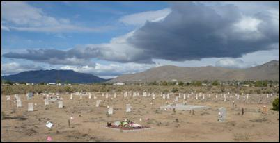 Photo of a cemetary with mountains in the backdrop.