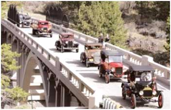 photo of vintage cars going over bridge
