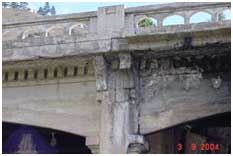 Close up photo of crumbling concrete bridge supports
