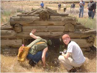 Photo of a couple of men leaning down to look into a old root cellar