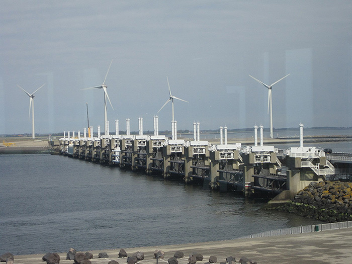Photo shows the massive, concrete and steel Eastern Scheldt storm surge barrier. Water is in the foreground and modern wind mills in the background.
