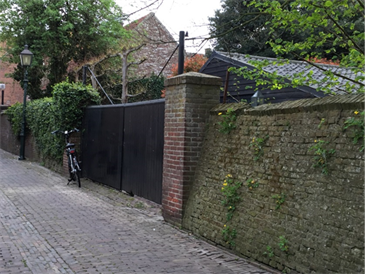 A bicycle rests on its kickstand on a cobble-stoned alleyway by a vine-covered brick fence.