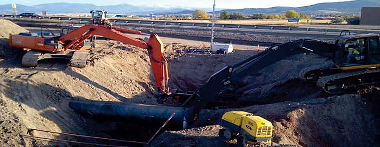 This is a photo two excavators digging a hole in the ground.