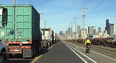 Cities face the ongoing challenge of accommodating increasing freight traffic on the same routes with other modes of travel. Here, a bicyclist is using a dedicated bike lane along a roadway heavily used by trucks in Seattle, WA.