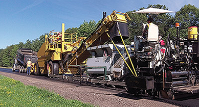 Photo. A material transfer vehicle moves an asphalt mixture from the delivery truck to the paver at a job site on State Highway 21 near Necedah, Wisconsin.