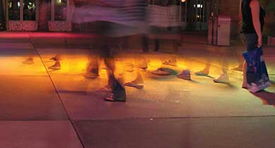Photo. A time-lapse image of a plaza with many pedestrians walking. The photo shows only the feet and legs of the pedestrians.