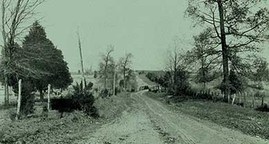 Historic photo. Short, sharp curves immediately precede and follow a narrow bridge on a dirt road.