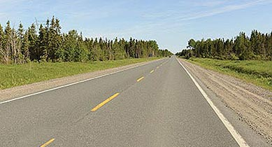 Photo. A two lane road with asphalt pavement