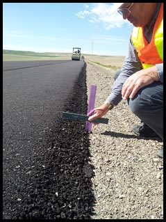 Jason Giard, an operations engineer in FHWA's Idaho Division, measures the height of a Safety EdgeSM treatment in Pocatello, Idaho.