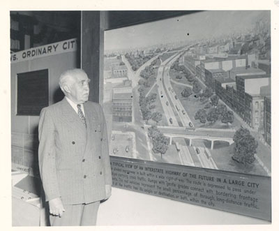 General Philip B. Fleming, Administrator of the Federal Works Agency, home of the Public Roads Administration (PRA), views PRA exhibit at the 1948 convention of the American Road Builders Association in Chicago.