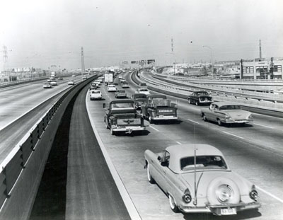 California - Traffic on the Santa Monica Freeway (I-10) near the intersection with the Santa Ana (I-105) and Golden State Freeways (I-5).  Note the use of the corrugated plastic shield on the median barrier rail.