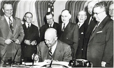 President Eisenhower signs the Federal-Aid Highway Act of 1954 on May 6, 1954. Watching are (left to right) Senator William F. Knowland (R-CA), Representative George A. Dondero (R-MI), Rep. Clifford Davis (D-TN), Senator Francis Case (SD), Rep. Homer D. Angell (R-OR), Senator Edward Martin (R-PA), and Rep. J. Harry McGregor (R-OH). On the fringe at far right is Rep. George H. Fallon (D-MD), who would play a key role in making the President's vision a reality in 1956. (Courtesy Dwight Eisenhower Library).