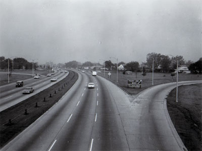 Interstate 94 (Edens Expressway) showing 6 traffic lanes, off ramp right and one ramp left, steel cable guard in median, Chicago, Illinois.