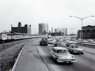 View of Northwest Expressway showing heavy traffic during peak period.  Looking East between Augusta Blvd.  And Division Street, C&NW RR on left. Chicago Illinois.