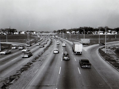 View of Congress Street Expressway looking East from Mannheim Road overpass showing heavy traffic and exit ramp right and enter ramp left.